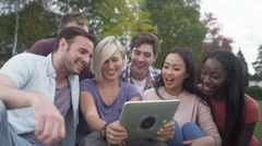 Happy group of friends in natural setting, pose for photo with computer tablet Stock Footage