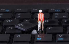 Miniature worker with drill working on keyboard Stock Photos
