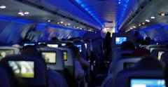 People watching in-flight entertainment inside passenger aircraft flight 4K UHD Stock Footage