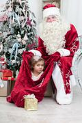 little girl looks out of a bag with santa nicolai's gifts - stock photo