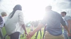 Happy Christian friends outdoors holding hands in circle & bowing heads to pray - stock footage