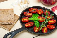 Stock Photo of baked cherry tomatoes with basil and thyme