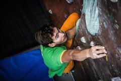 Muscular man practicing rock-climbing on a rock wall indoors Stock Photos