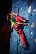 Young woman practicing rock-climbing on a rock wall indoors Kuvituskuvat