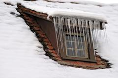 Icicles at the dormer of a roof Stock Photos