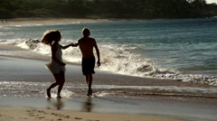 Fun loving young couple stroll the beach in Maui, Hawaii Stock Footage