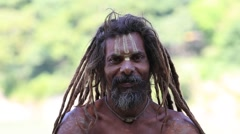 Indian sadhu holy man sits on the ghat along the Ganges river. Rishikesh, India Stock Footage