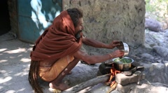 Sadhu holy man preparing  meal on a fire along  Ganges river.  Rishikesh, India - stock footage