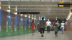Commuters walking in subway tunnel train station corridor for pedestrians inside Stock Footage