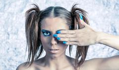 Stock Photo of Beautiful model with pigtails, fancy makeup and blue manicure