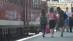Commuters with backpack and hand luggage walking near stationary train, arrival Stock Footage