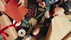 Hands wrapping Christmas presents arial view Stock Footage