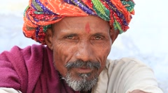 Indian man, sits on the ghat along the sacred Sarovar lake. Pushkar, India - stock footage