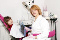 Female dentist with x-ray and little girl patient Stock Photos