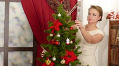 Woman decorate Christmas tree at home Stock Footage