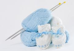 Knitted handmade baby's bootees, ball of yarn, needles Stock Photos