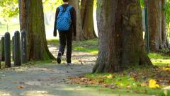 Teenage boy with rucksack walking in park Stock Footage