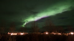 Green northern lights aurora glow through clouds cabin house forest, Iceland Stock Footage