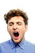portrait of a young man yawning over white background - stock photo