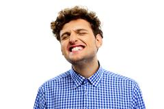 man showing his teeth over white background - stock photo