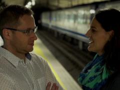 Couple waiting for subway and talking on platform, steadycam shot Stock Footage