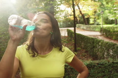 Happy jogger drinking energy drink after run, steadycam shot Stock Footage