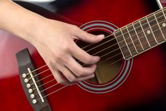 Photo of woman's hand on guitar Stock Photos