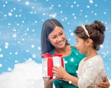 happy mother and child girl with gift box - stock photo