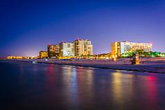 view of beachfront hotels and the beach from the fishing pier at night in cle - stock photo