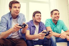 Smiling friends playing video games at home Stock Photos