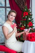 Woman with gift box under tree at home Stock Photos