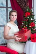 Stock Photo of woman with gift box under tree at home