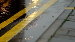 Double yellow lines in the rain with car light reflections Stock Footage