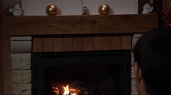 Young Man Sitting In Front Of A Fireplace Stock Footage