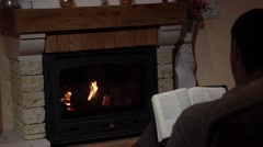 Stock Video Footage of Young Man Reading The Bible In Front Of A Fireplace Belief Concept