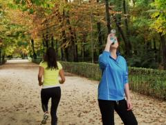Jogger drinking energy drink in the park, steadycam shot Stock Footage