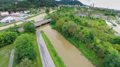 Aerial shot of muddy river flooding under railway bridge Stock Footage