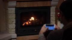 Young Man Is Writing An SMS In Front Of A Fireplace Communication Concept Stock Footage