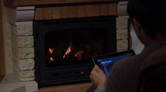Man Is Using His Tablet In Front Of A Fireplace Technology and Home Concept Stock Footage