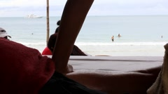 Close up womans hand makes a man foot massage on the beach of Koh Samui in Stock Footage
