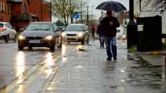 Man walking with umbrella in rain and cars passing Stock Footage