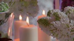 Close-up of lighted candles on flowers backdrop Stock Footage