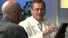 Male doctor explaining information with tablet - close - stock footage
