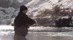 Slow motion shot of a fly fisherman casting out his line and lure - stock footage