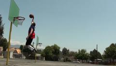 Slow motion of basketball player slam dunking in school yard - stock footage