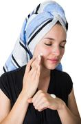 beautiful young woman applying cleaning cream moisturizer to her face - stock photo