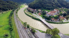 Flying over river making curve through town to valley Stock Footage