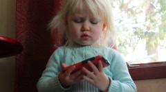 Toddler settles in with smart phone then plays Stock Footage