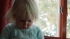 Two year old looks down at her lap while focused Stock Footage