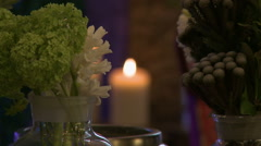 Fresh cut flowers on background of lighted candle - stock footage